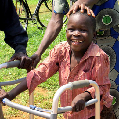 A smiling child with a walking aid